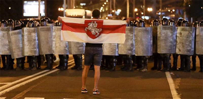 מפגין מול כוחות המשטרה במינסק, בלארוס / צילום: Sergei Grits, AP
