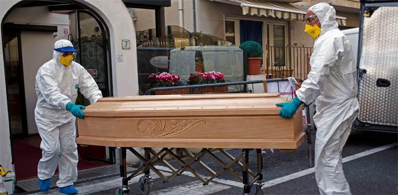 צוות רפואי באיטליה נושא ארון של קורבן קורונה / צילום: AP Photo, AP
