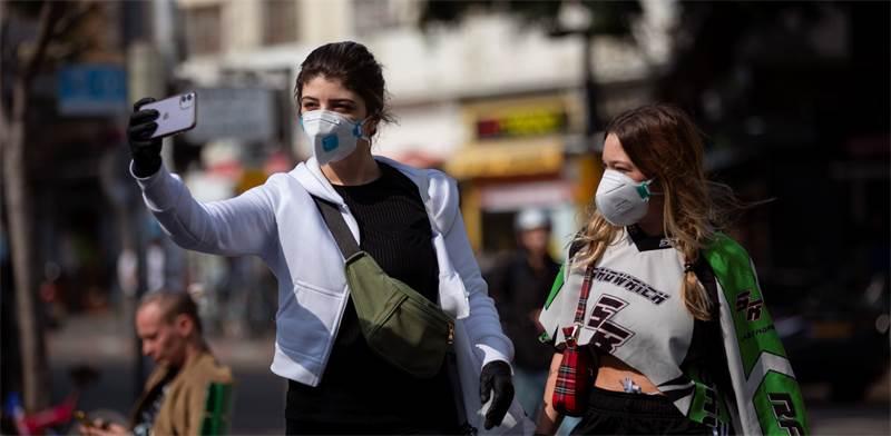 """צעירות עם מסכות בת""""א / צילום: Oded Balilty, AP"""
