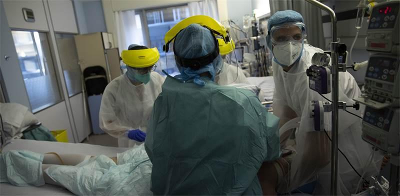 צוות רפואי מטפל בחולה קורונה בבית חולים בבלגיה / צילום: Francisco Seco, AP