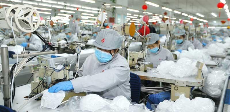 עובדים חובשים מסכות במפעל סיני לייצור מסכות /  צילום: Liang Xiaopeng  AP