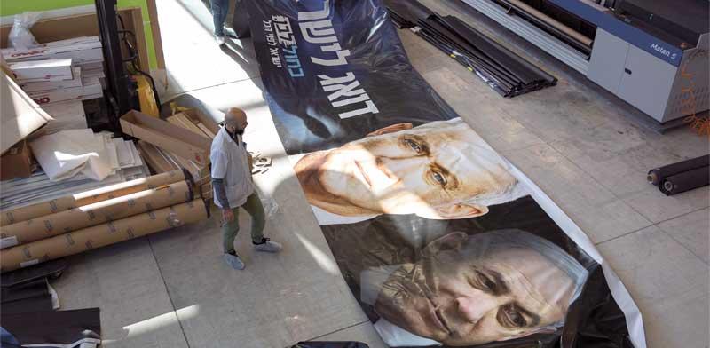 נתניהו וגנץ על שלטי בחירות של כחול לבן בבית הדפוס / צילום: AP - עודד בלילתי