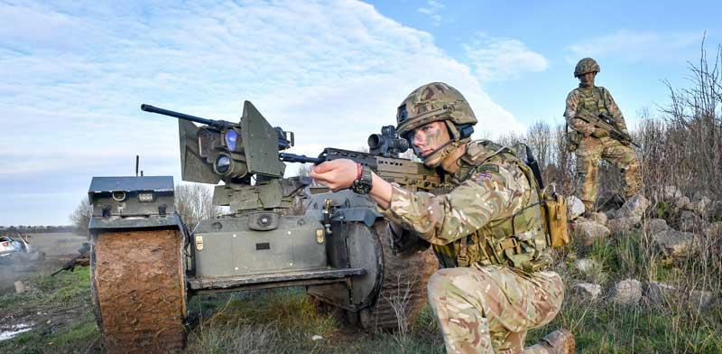 """מכונת ירייה אוטונומית לצד חייל נאט""""ו / צילום: רויטרס"""