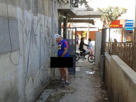 ישראלי עושה את צרכיו בכניסה לבית במהלך המרתון בת